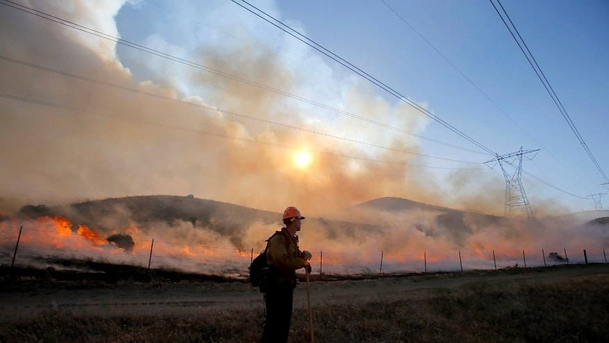 A firefightier watches a backfire set in Hungry Valley State Park to halt the prgress of the Grand fire, which charred more than 3,000 acres of wildlands near Frazier Park on Wednesday, May 15, 2013. Cooler temperatures and lighter winds are helping hundreds of firefighters combat a 3,000-acre wildfire. (AP Photo/Los Angeles Times, Luis Sinco) OUTS; ORANGE COUNTY REGISTER, LA DAILY NEWS, VENTURA COUNTY STAR, INLAND VALLEY DAILY BULLETIN, LA OPINION), SOMETIMES: -CALON (LONG BEACH PRESS-TELEGRAM) NO FORNS, NO SALES, MAGS OUT, MANDATORY CREDIT