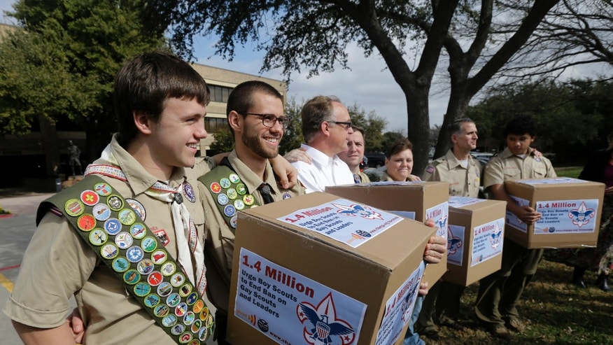 Feb. 4, 2013: In this file photo, James Oliver, left, hugs his brother and fellow Eagle Scout, Will Oliver, who is gay, as Will and other supporters carry four boxes filled with petitions to end the ban on gay scouts and leaders in front of the Boy Scouts of America headquarters in Dallas, Texas.
