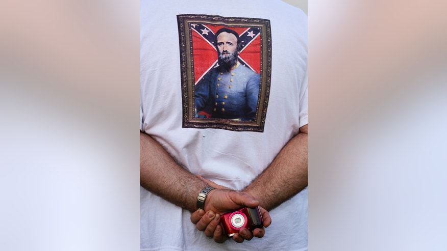 "A visitor wears a shirt with General Stonewall Jackson printed on it during a National Park Service event at the site of the home where General Stonewall Jackson died on Friday, May 10, 2013 in Caroline County, Va. Scholars have long questioned whether it was an infection or pneumonia that killed Jackson, who gained the nickname ""Stonewall"" early in the war and went on to be lionized in the South and feared in the North because of his military exploits. On Friday, the 150th anniversary of Jackson's death, a trauma surgeon with experience on the battlefield in Iraq and Afghanistan will reveal his diagnosis of Jackson's death after reinvestigating the medical record. After reviewing the 1860s files and subsequent reports, University of Maryland surgeon and professor Joseph DuBose told The Associated Press that Jackson most likely died of pneumonia. (AP Photo/The Free Lance-Star, Elijah Nouvelage)"