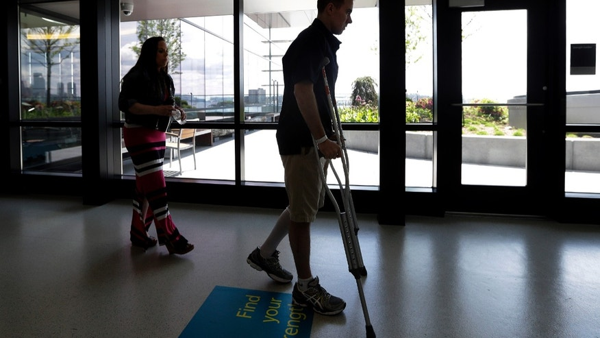 MBTA Police Officer Richard Donahue makes his way on crutches as his wife, Kim, follows him out of the gym at Spaulding Rehabilitation Hospital in Boston's Charlestown section, Sunday, May 19, 2013. Donahue almost lost his life after being shot during the crossfire with the Boston Marathon bombing suspects in Watertown, Mass. (AP Photo/Elise Amendola)