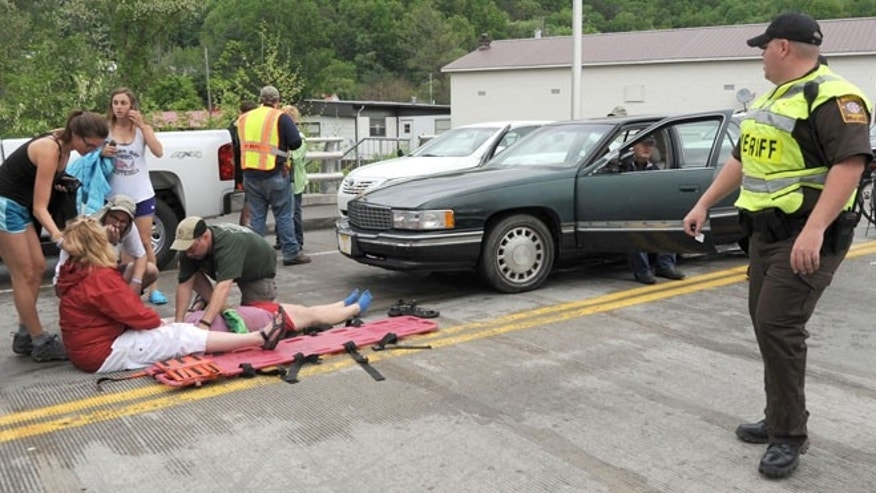 May 18, 2013: Emergency personnel respond to one of the people hit by a car, at right, during the beginning of the Hikers Parade at the Trail Days festival in Damascus, Va.
