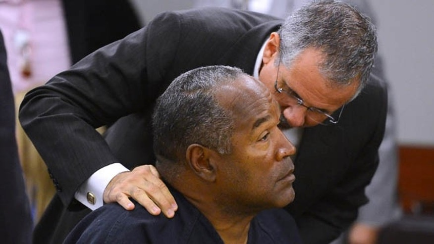 May 17, 2013: O.J. Simpson and his defense attorney Ozzie Fumo confer during an evidentiary hearing for Simpson in Clark County District Court in Las Vegas. Simpson, who is currently serving a nine-to-33-year sentence in state prison as a result of his October 2008 conviction for armed robbery and kidnapping charges, is using a writ of habeas corpus to seek a new trial, claiming he had such bad representation that his conviction should be reversed.