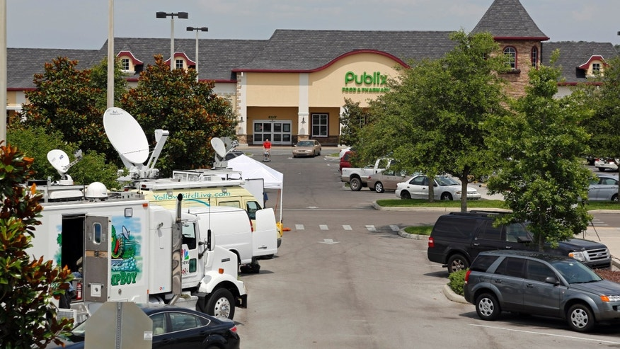 Satellite trucks line the parking lot where the highest Powerball jackpot worth an estimated $590.5 million was sold recently at this Publix supermarket located in Zephyrhills, Fla. on Sunday  May 19, 2013. (AP Photo/Scott Iskowitz)