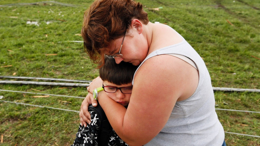 Rebekah Stuck hugs her son, Aiden Stuck, 7, after she found him in front of the destroyed Briarwood Elementary after a tornado struck south Oklahoma City and Moore, Okla., Monday, May 20, 2013. Aiden Stuck was inside the school when it was hit. (AP Photo/ The Oklahoman, Nate Billings)