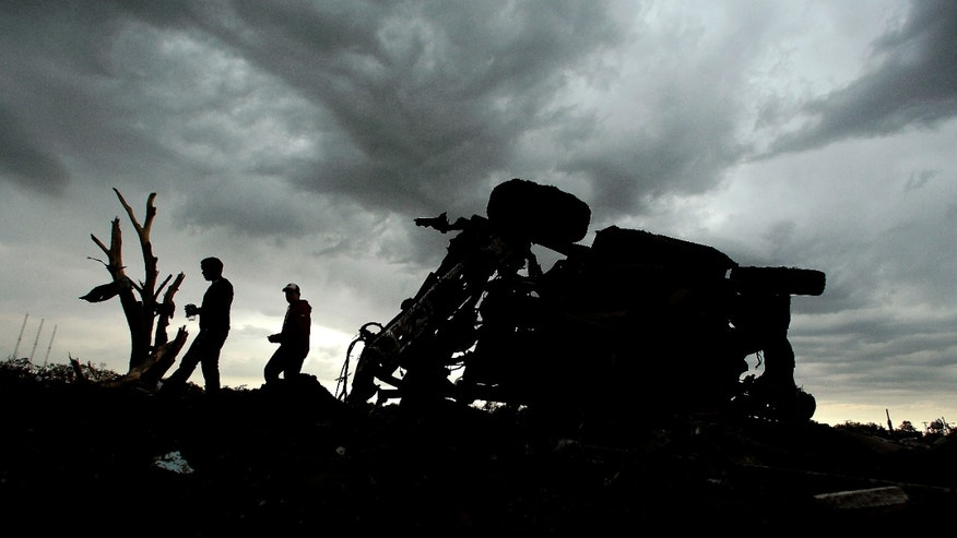 Residents pass a destroyed car as they walk through a tornado-ravaged neighborhood Tuesday, May 21, 2013, in Moore, Okla. A huge tornado roared through the Oklahoma City suburb Monday, flattening entire neighborhoods and destroying an elementary school with a direct blow as children and teachers huddled against winds. (AP Photo/Charlie Riedel)