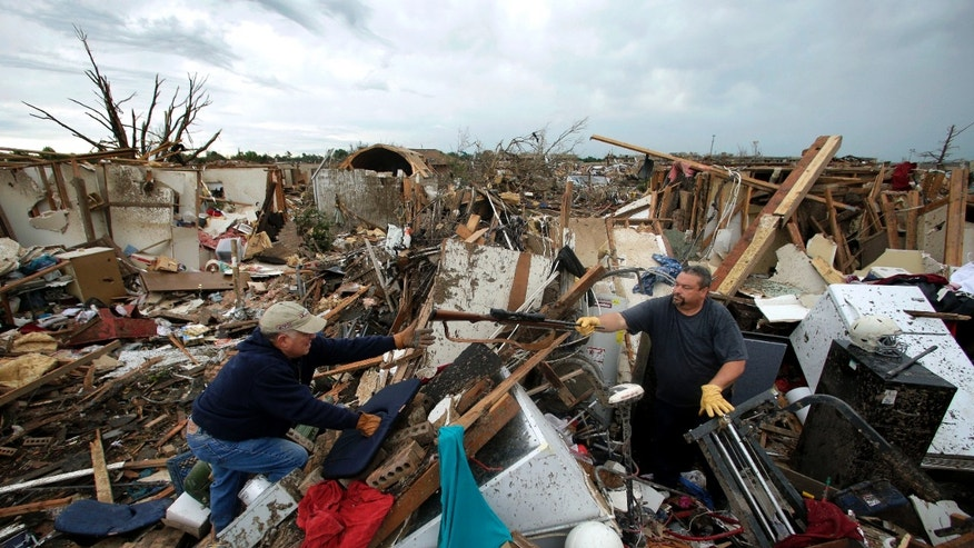 Dalton Sprading, right, hands a gun to his uncle Roger Craft as he salvages items from his tornado-ravaged home Tuesday, May 21, 2013, in Moore, Okla.  A huge tornado roared through the Oklahoma City suburb Monday, flattening an entire neighborhoods and destroying an elementary school with a direct blow as children and teachers huddled against winds. (AP Photo/Charlie Riedel)