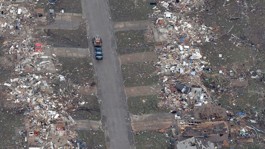 An aerial view of a street lined by homes destroyed by Monday's tornado is shown Tuesday, May 21, 2013, in Moore, Okla. At least 24 people, including nine children, were killed in the massive tornado that flattened homes and a school in Moore, on Monday afternoon. (AP Photo/Tony Gutierrez)