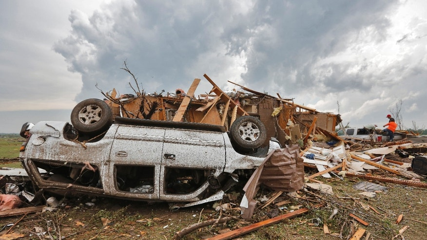 A demolished home with the car flipped over is all that remains left behind in the damage from the tornado that hit the area near 149th and Drexel on Monday, May 20, 2013 in Oklahoma City, Okla. (AP Photo/ The Oklahoman, Chris Landsberger)