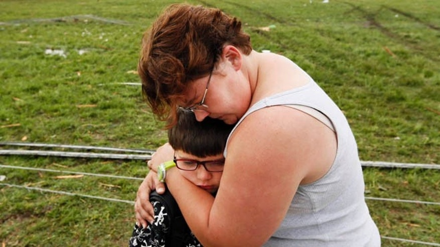 May 20, 2013: Rebekah Stuck hugs her son, Aiden Stuck, 7, after she found him in front of the destroyed Briarwood Elementary after a tornado struck south Oklahoma City and Moore, Okla. Aiden Stuck was inside the school when it was hit.