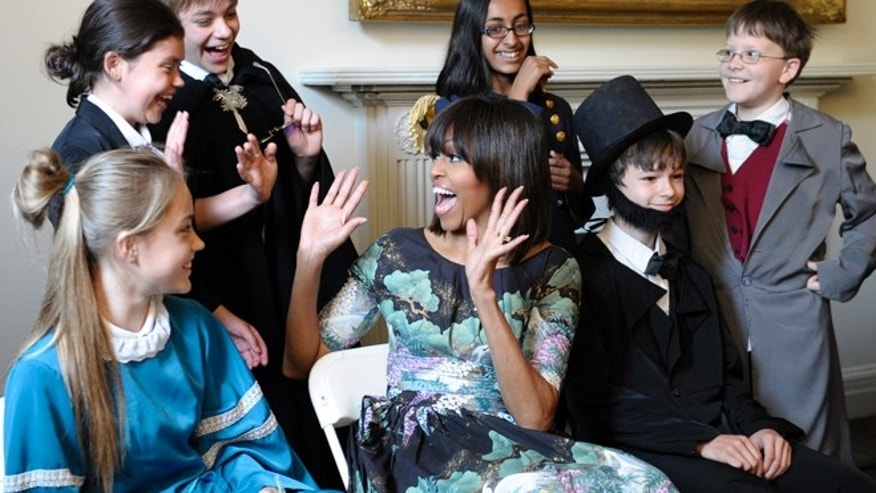 May 22, 2013: First lady Michelle Obama reacts as she surprises schoolchildren from Willow Springs Elementary School in Fairfax, Va., before they performed part of a play at the Decatur House, a National Trust for Historic Preservation Site and home to the David M. Rubenstein National Center for White House History, in Washington.