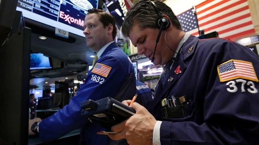 April 29, 2013: Specialist Gregg Maloney, left, and trader John Panin work on the floor of the New York Stock Exchange