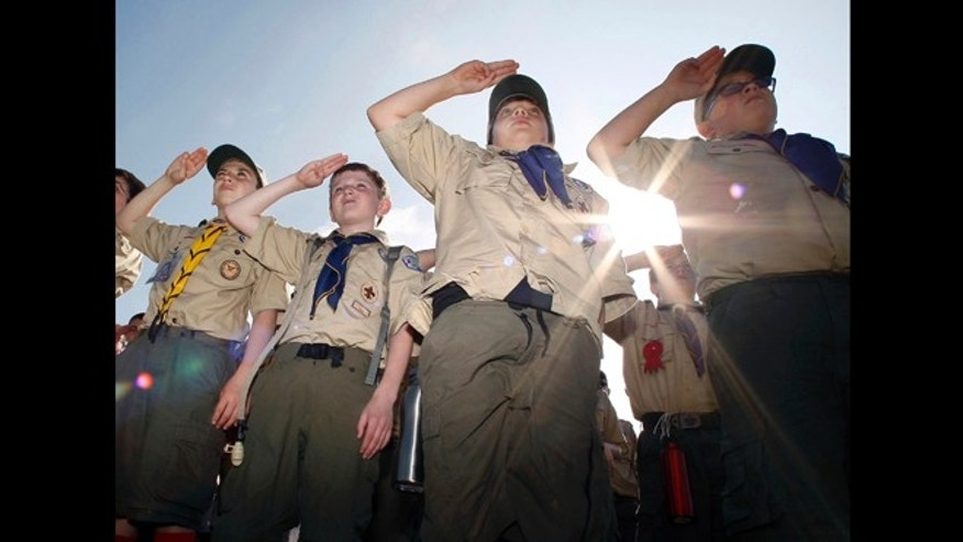 Boy Scouts salute early Saturday morning, May 21, 2011 during New Jersey's Boy Scouts Camporee in Sea Girt, N.J. The Boy Scouts of America's National Council has voted to ease a long-standing ban and allow openly gay boys to be accepted as Scouts, Thursday, May 23, 2013.