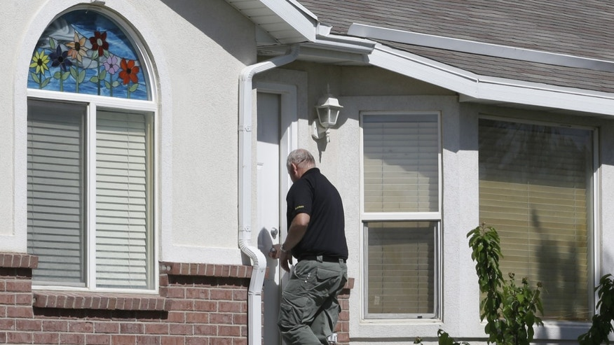 A law enforcement official from Davis County walks in to the home where two young boys were found dead Thursday, May 23, 2013, in West Point, Utah. A teenager was arrested Thursday in the deaths of his two younger brothers, ages 4 and 10, at the family home in a Utah subdivision of new homes and tidy lawns, police said. Davis County Sheriff Todd Richardson said authorities believe the boys died from knife wounds. It appears the 15-year-old boy acted alone, he said.  (AP Photo/Rick Bowmer)