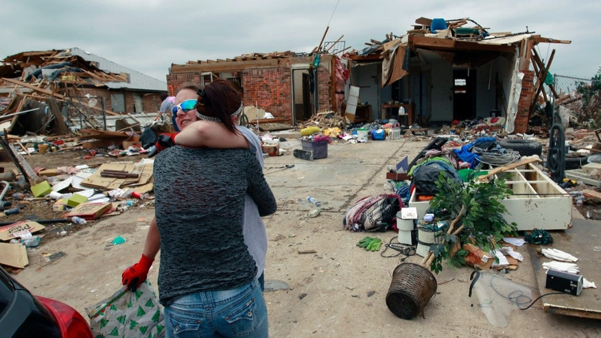 Sabrina Mitchell, age 19, hugs her cousin Rachel DeBord, who helps Mitchell salvage items from her home which was destroyed earlier in the week when a tornado hit Moore, Okla., Friday, May 24, 2013. Mitchell and her family survived the tornado inside a neighbor's storm shelter.(AP Photo/Brennan Linsley)