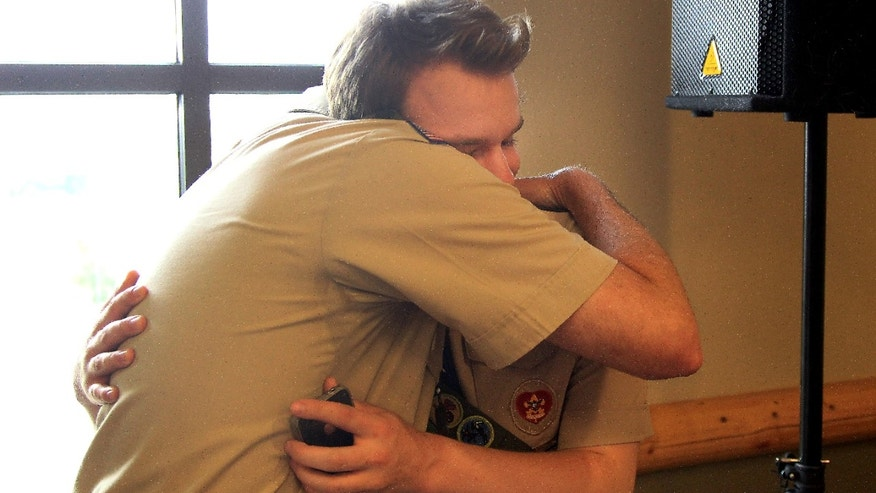 Boy Scout Pascal Tessier receives a hug from Greg Bourke, a scout leader from Louisville, Ky, after hearing of the announcement by Boy Scouts of America passing a resolution allowing scouts that are openly gay into their ranks. Mr. Tessier was in the command post for the group, Scouts for Equality at Great Wolf Lodge in Grapevine, Texas on Thursday, May 23, 2013. Tessier is a life scout who was unable to finish his eagle scout unless the resolution passed. (AP Photo/The Dallas Morning News, Brad Loper)