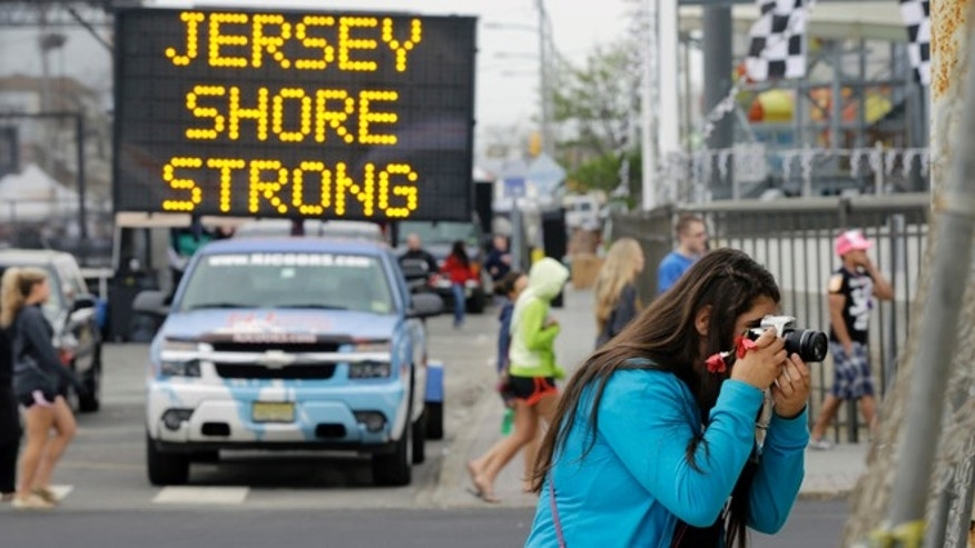 May 18, 2013: Angelina Zuzuro, 16, of Denville, takes photos near a sign in Seaside Heights, N.J.. The boardwalks are back, and so are most of the beaches, even if some are a little thinner this year. The smell of funnel cakes, french fries and pizza will mingle with the salt air, and the screech of seagulls will be heard. But so will the thwack of hammers repairing what can be fixed and the roar of bulldozers and backhoes tearing down what cant. Welcome to Summer 2013 at the Jersey shore, the first since Superstorm Sandy pummeled the coast and upended hundreds of thousands of lives. (AP/Mel Evans)
