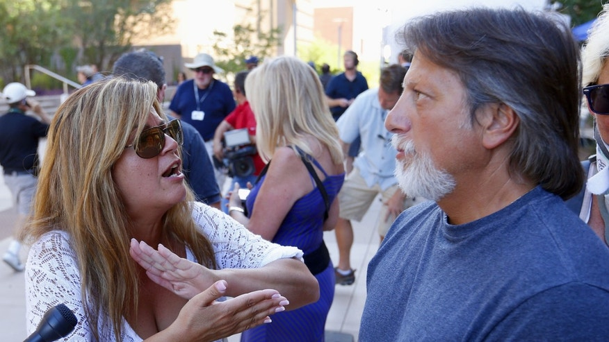 Gee Russo, left, argues with her husband Mark Russo, who favored the death penalty for Arias, both of North Caldwell, N.J., after it was announced the jury deadlocked on the penalty phase of the Jodi Arias murder trial out in front of Maricopa County Superior Court on Thursday, May 23, 2013, in Phoenix.  Jurors who spent five months determining Jodi Arias' fate couldn't decide whether she should get life in prison or die for murdering her boyfriend, Travis Alexander in his suburban Phoenix home. (AP Photo/Ross D. Franklin)