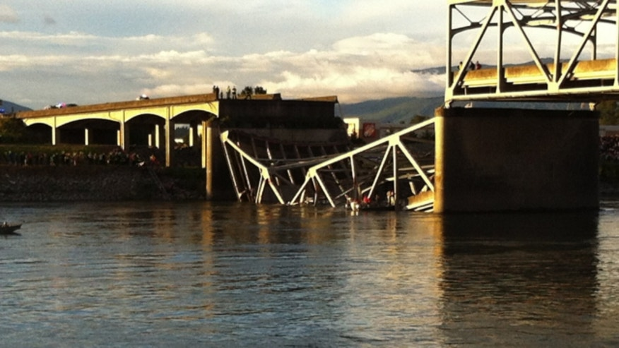 May 23, 2013: People look on after the Interstate 5 bridge collapsed over the Skagit River in Mount Vernon, Wash.