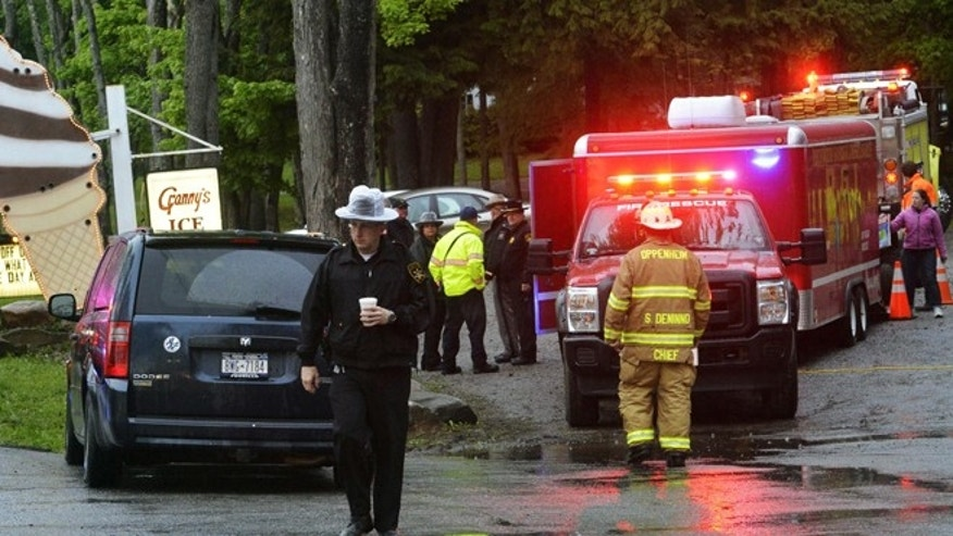 In this Friday, May 24, 2013 photo, rescue workers move about the staging area at Granny's Ice Cream across from the site of a plane crash in a wooded area off Route 10 in the town of Fulton in Ephratah, N.Y., after a small plane crashed killing two people.