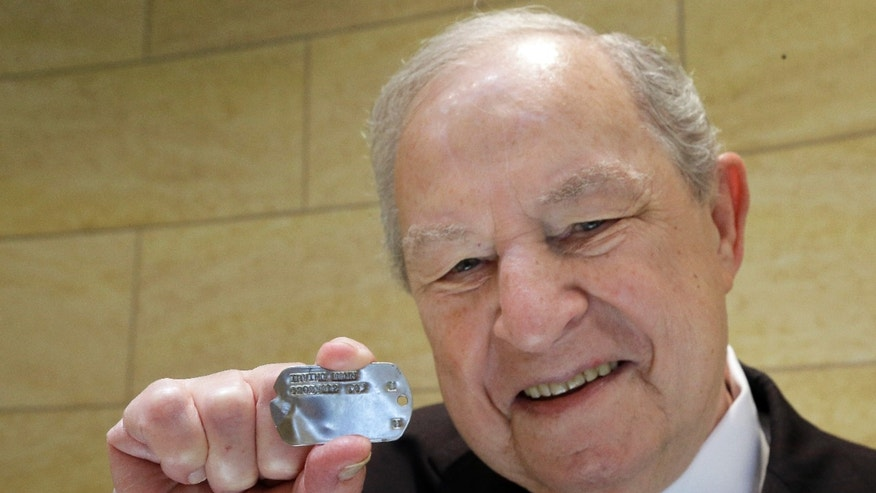 In this Wednesday, May 22, 2013 photo, World War II veteran Irving Mann poses for a photo with his dog tag that was found and returned to him, in Rochester, N.Y. Mann says he was skeptical when an email from a French woman recently arrived at his Rochester jewelry store. She said she'd found the tag in her barley field and was looking for its owner. (AP Photo/David Duprey)