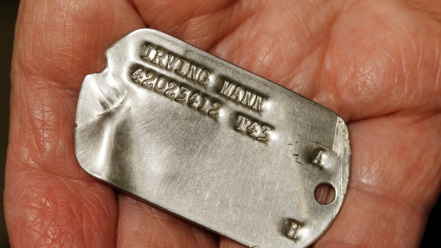In this Wednesday, May 22, 2013 photo, World War II veteran Irving Mann displays his dog tag that was found and returned to him, in Rochester, N.Y. Mann says he was skeptical when an email from a French woman recently arrived at his Rochester jewelry store. She said she'd found the tag in her barley field and was looking for its owner. (AP Photo/David Duprey)