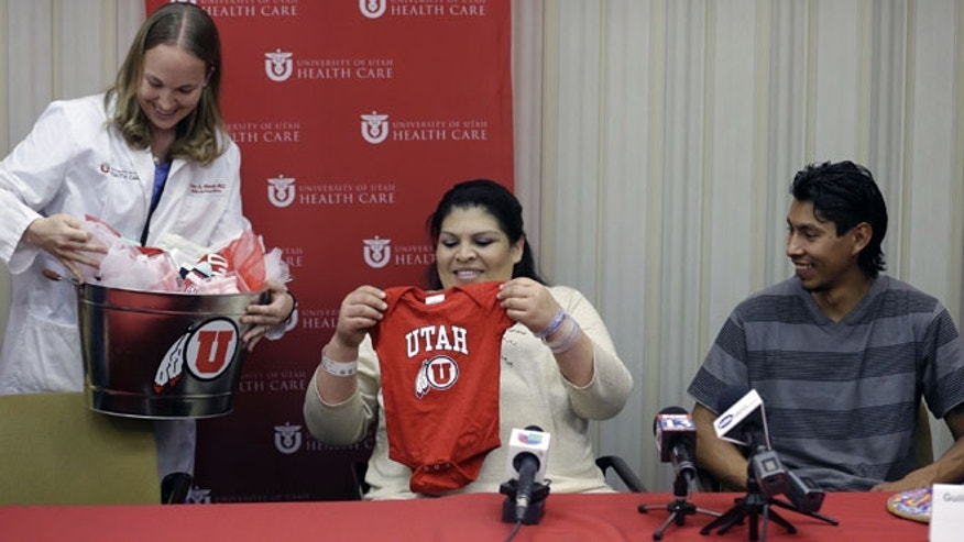 May 28, 2013: Dr. Tracy Manuck, left, gives a baby present to Guillermina and Fernando Garcia after  a news conference at the University of Utah hospital, in Salt Lake City. A team about 40 medical personnel led by eight doctors helped ensure a Utah couple's newborn quintuplets were born healthy.