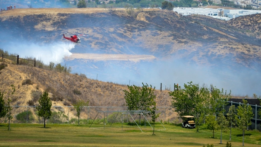 A helicopter makes a drop on a brush fire that broke out behind the Six Flags Magic Mountain park Tuesday, May 28, 2013 in Valencia, Calif.  Crews are chasing a new fire north of Los Angeles and are working to increase containment of a rural San Diego County blaze. (AP Photo/Los Angeles Daily News, David Crane)  NO SALES; MAGS OUT; HILLS OUT, LOS ANGELES TIMES OUT; VENTURA COUNTY STAR OUT ANTELOPE VALLEY PRESS OUT