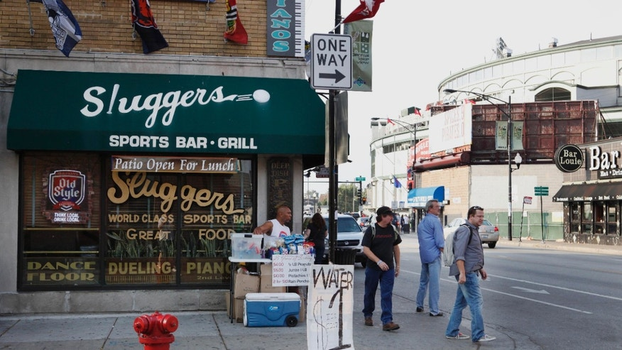 FILE - This Sept. 21, 2010 file photo shows Sluggers Sports Bar and Grill near Wrigley Field, background, before a Chicago Cubs baseball game in Chicago. On Thursday, May 30, 2013, Sami Samir Hassoun, a Lebanese immigrant, is scheduled to be sentenced at federal court in Chicago for placing a backpack he thought held a bomb outside the bar in September 2010. Prosecutors want a 30-year prison sentence for the 25-year-old, who pleaded guilty to weapons charges last year. The defense filing argues Hassoun deserves no more than 20 years, in part because they contend he was egged on by an FBI informant to concoct the bombing scheme. (AP Photo/Charles Rex Arbogast, File)