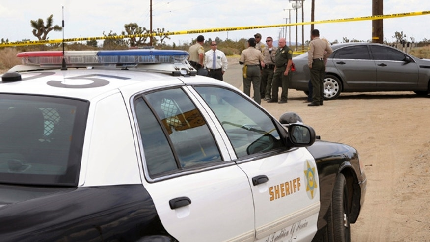 May 9, 2013: Los Angeles County Animal Care and Control and Sheriff personnel congregate near the area where a 63-year-old female jogger was attacked and killed by four pit bulls near Avenue S and 115th Street East in Palmdale, Calif.
