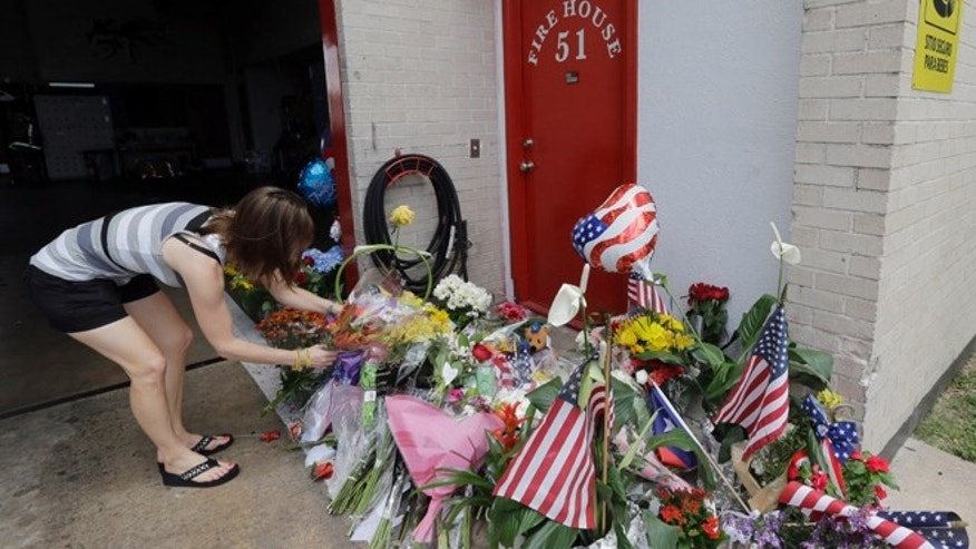 June 1, 2013: Shannon Neira places flowers at a makeshift memorial at Houston Fire Station 51 in Houston. Four firefighters searching for people they thought might be trapped in a blazing Houston motel and restaurant Friday were killed when part of the structure collapsed and ensnared them, authorities said.