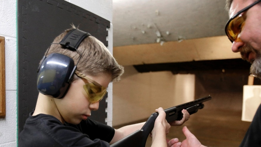 In this photo, Dan Blackford, right, shows Rory Strain, 12, how to hold a shotgun at a shooting range in Houston. Strain lives in the northwest Houston community of Oak Forest, the first residential area being trained and equipped by a nonprofit that is giving away free shotguns to single women and neighborhoods with high crime rates.