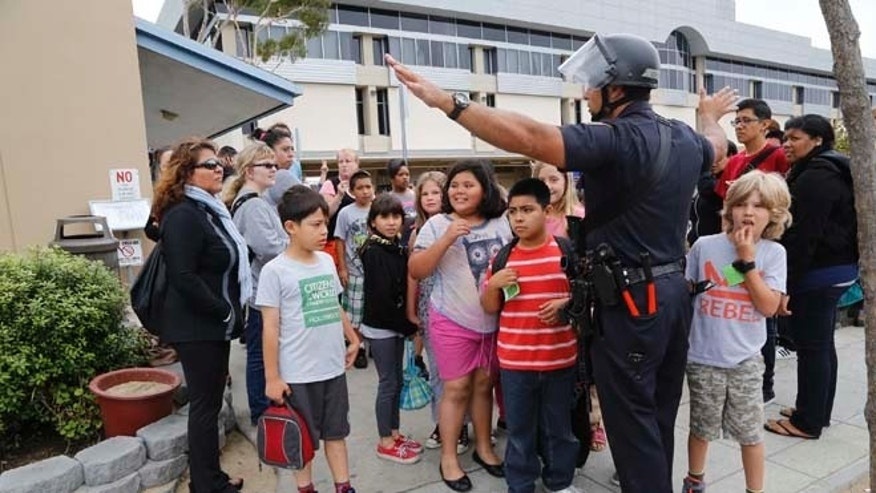 June 7, 2013: A Santa Monica police officer leads children from Citizens of the World School in Los Angeles out of Santa Monica College, who were there for a planetarium show, as the campus is systematically cleared, in Santa Monica, Calif.