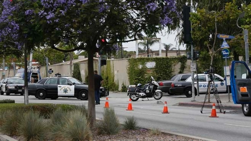 June 7, 2013: Police stand outside the locked down  Santa Monica College campus in Santa Monica, Calif.