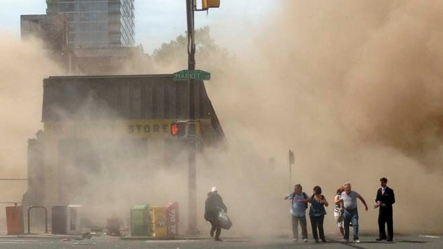 June 5, 2013: In this photo provided by Jordan McLaughlin, a dust cloud rises as people run from the scene of a building collapse on the edge of downtown Philadelphia. (AP)