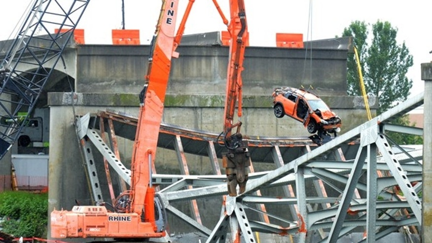 May 27, 2013: Washington State DOT and contract workers removed the SUV and Pickup truck from the deck of the collapsed Skagit River bridge in Mount Vernon, Wash. A trailer that was under tow by the the pickup truck was removed the night before. Drivers of the the two vehicles traveling over the Skagit River Thursday evening were unable to stop before heading onto the collapsing deck as it crashed into the river below. Three people were rescued and there were no fatalities.