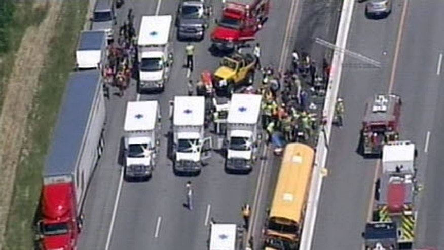 June 11, 2013: In this image taken from video from WHAS11-TV, emergency crews respond to a crash involving a bus carrying students on a college campus visit on on Interstate 64 near the Shelby County line in Louisville, Ky. The bus was a charter service and had 42 students aboard, said Jefferson County public schools spokesman Ben Jackey.