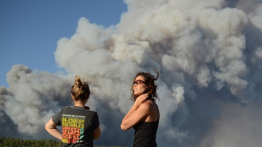 June 11, 2013: The Black Forest Fire burns northeast of Colorado Springs, Colo., as nearby residents Amy O&#39&#x3b;Connor, left, and Nathalie Bartleson watch it creep toward the tree line.