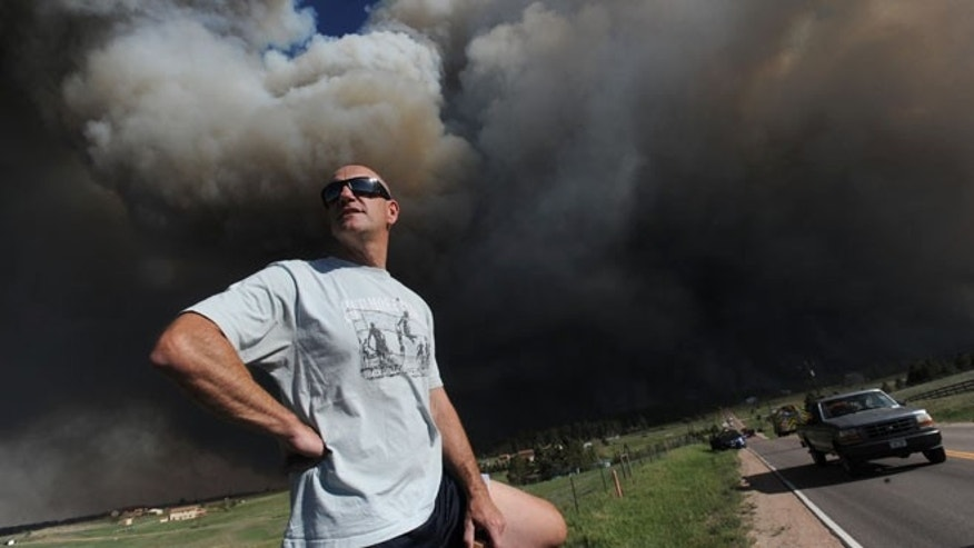 June 11: Dave Dunlap watches from the bed of his truck as a wildfire crosses Black Forest Road near his home in Colorado Springs.