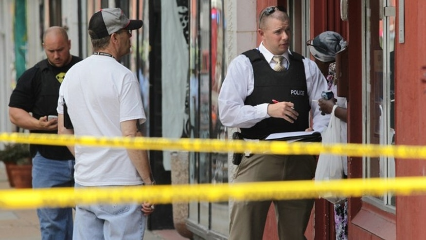 June 13, 2013: St. Louis police work the scene where four people were found dead in a business along Cherokee Street south of downtown in St. Louis.