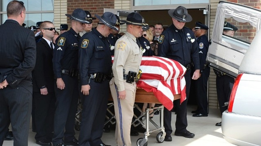 May 30, 2013: The body of fallen Bardstown police officer Jason Ellis, who was killed in an ambush slaying on May 25, 2013, is placed in a hearse during his funeral at the Parkway Baptist Church in Bardstown, Ky.