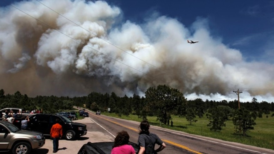 June 12, 2013: People pulled to over watch from their cars as a fire-fighting slurry plane makes a pass in preparation to drop its load on a wildfire in the Black Forest area north of Colorado Springs, Colo.