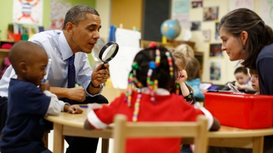 February 14, 2013: President Obama uses a magnifying glass to play a game with children in a pre-kindergarten classroom at College Heights early childhood learning center in Decatur, Georgia.