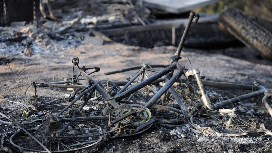 June 13, 2013: The remains of a mountain bike lays in the ashes outside a house along Holmes Road during the third day of the Black Forest Fire north of Colorado Springs, Colo.