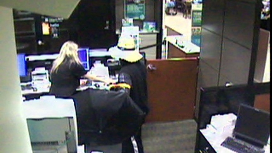 June 16, 2013: An image form a surveillance video released by the South Strabane Township Police shows a robbery, at the Citizens Bank inside the Giant Eagle at Strabane Square in South Strabane Township, Pa., by a man in a floppy hat.  The suspect fatally shot a supermarket customer who ran after him and tried to stop his getaway car, police said.
