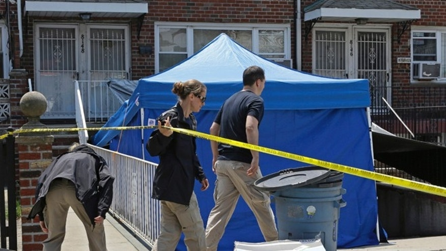 June 18, 2013: FBI agents duck under crime scene tape in front a New York city house once occupied by a famous gangster in New York.