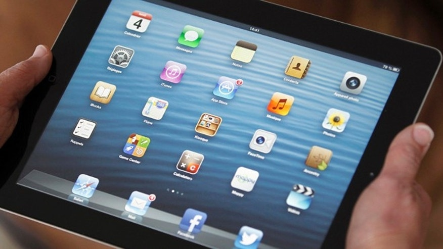 An illustration picture shows application icons on an Apple Ipad tablet held by a woman in Bordeaux, Southwestern France, February 4, 2013.  F