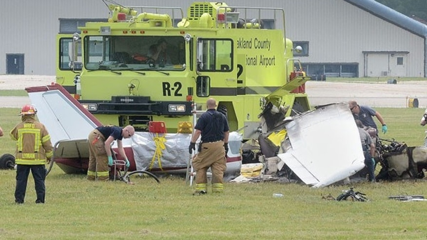 June 21, 2013: Emergency personnel looks over the scene of a plane crash at Oakland International Airport in Waterford, Mich.  A pilot and three passengers have were killed after a small plane crashed shortly after takeoff from the airport northwest of Detroit.