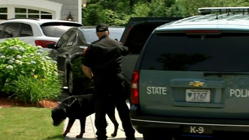 June 22, 2013: In this image taken from video, a state police officer and dog arrive outside the home of New England Patriots football player Aaron Hernandez in North Attleboro, Mass.