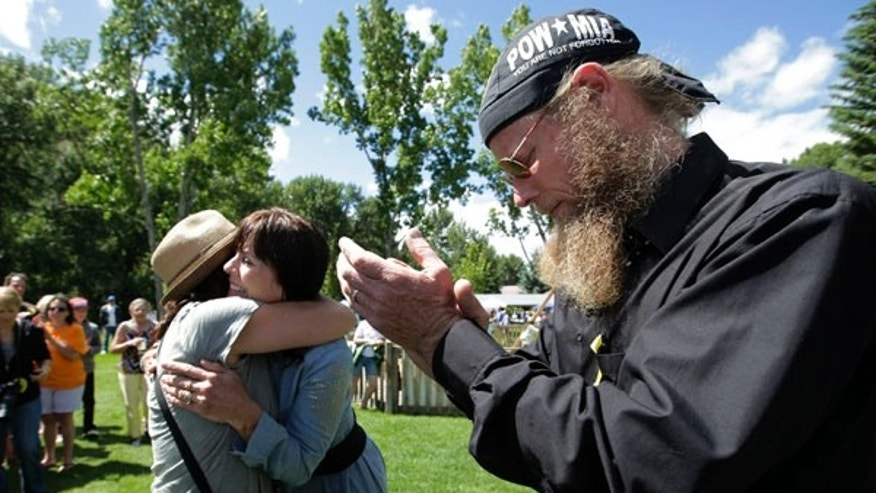 June 22, 2013: Bob Bergdahl, right, and wife, Jani, center, the parents of captive U.S. Army Sgt. Bowe Bergdahl, are comforted by a supporter at the 'Bring Bowe Back' celebration held to honor Sgt. Bergdahl in Hailey, Idaho.