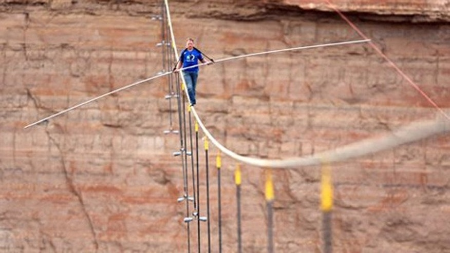 June 23, 2013: In this photo provided by the Discovery Channel, aerialist Nik Wallenda walks a 2-inch-thick steel cable taking him a quarter mile over the Little Colorado River Gorge, Ariz.